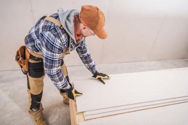 Male Construction Contractor Prepares Sheetrock Installation.