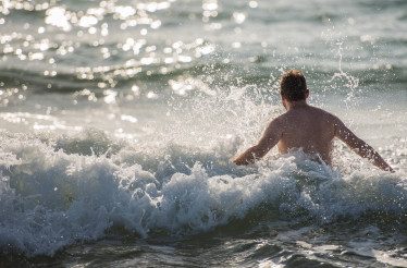 Caucasian Man Diving In Ocean Waves.