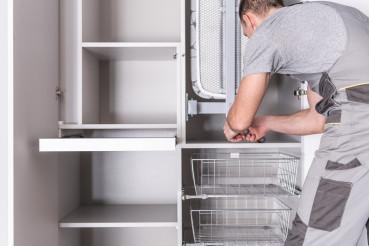 Caucasian Handyman Finishes Installation Of Walk In Closet.