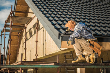 Male Roof Contractor Reviews Project Progress.