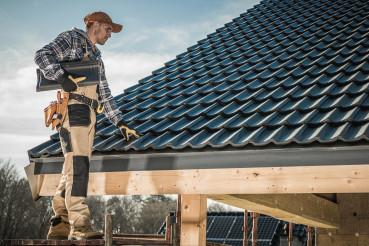 Male Worker Installing Roof Shingles.