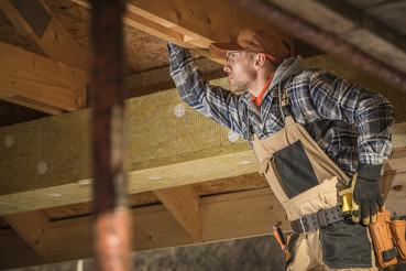 Caucasian Worker Checks Wooden Framing Of New Attic.