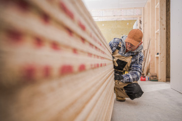 Carpenter Looks At Wooden Boards Needed For Job.