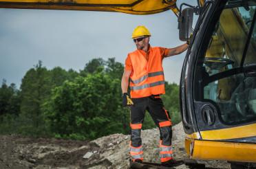 Machine Operator Standing On Hydraulic Excavator Assessing Job Site.