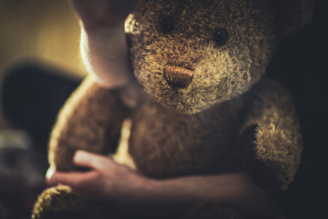 Close View Of Teddy Bear Toy In Child Arms.