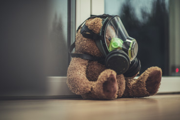Toy Teddy Bear With Protective Mask By The WIndow.