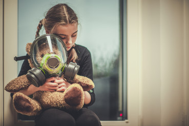 Toy Bear With Gas Mask Embraced By Young Girl.