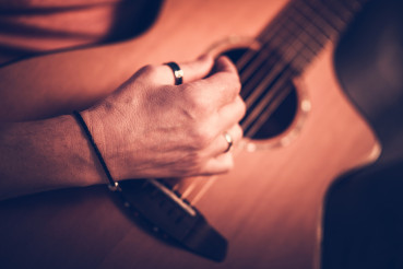 Male Musician Playing On Acoustic Guitar While Sitting Down.