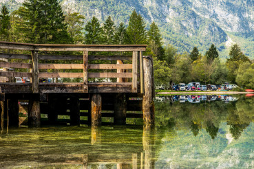 Panoramic View Of Mountains Lake And Wooden Pier In Slovenia.