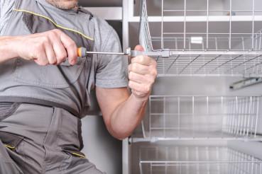 Close Up Of Handyman Fastening Parts Of Metal Closet Basket.
