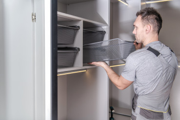 Male Handyman Finishes Installation Of Walk In Closet And Storage Area.