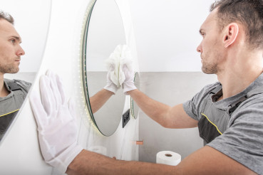 Male Caretaker Cleans Mirrors In Residential Household.