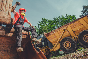 Caucasian Constrcution Worker Sitting And Resting On Top Of Backhoe.