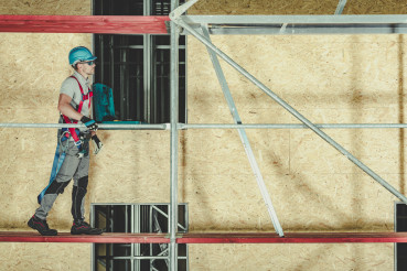 Construction Worker Walking On Scaffolding
