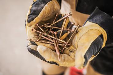 Bundle Of Golden Screws In Man's Hands.