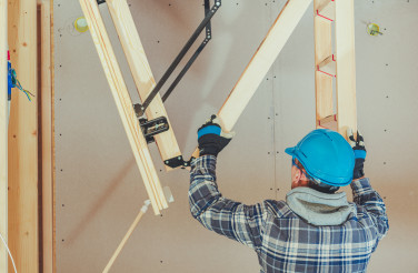 Male Handyman Attaches Parts Of Wooden Access Ladder.