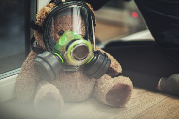 Teddy Bear Wearing Gas Mask During Pandemic With Girl Looking Out Window.