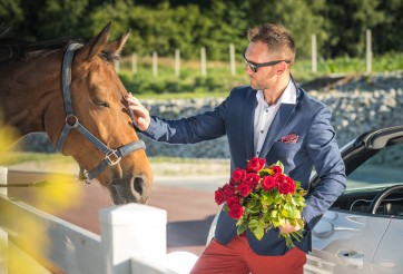Handsome Man With Bouquet Of Red Roses Petting Horse.