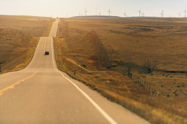 Long Colorado Highway With Wind Mills In Background.