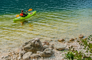 Caucasian Male Kayaking In Clear Waters Of Lake.