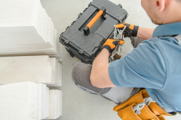Male Building Contractor Sorts Through Toolbox To Find Needed Materials.