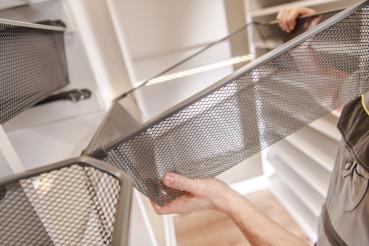 Man Installing Metal Basket In Closet Cabinet.