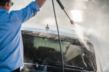 Cacuasian Auto Wash Worker Cleans Client Car.