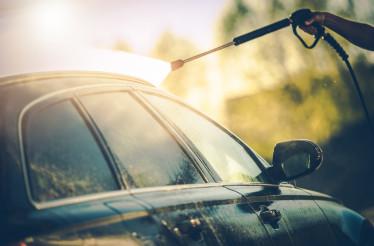 Close Up Of Man Washing Car With Hose.
