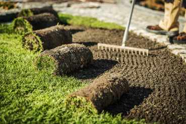 Lawn Care Contractor Prepares Area For Sod Installation.