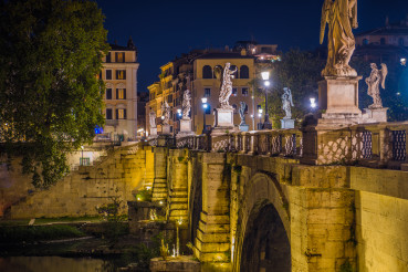 Night View Of Bridge Angel Statues And Buildings In Rome.