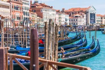 Row Of Venetian Gondolas Parked At Wooden Dock.