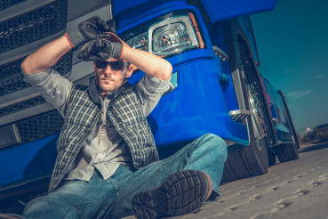 Male Trucker Sitting On Ground At Rest Stop Area.