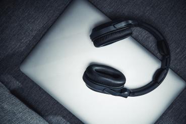 Wireless Headphones On Top Of Laptop Computer.