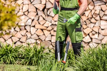 Caucasian Gardener Worker Holding Hand Tools.
