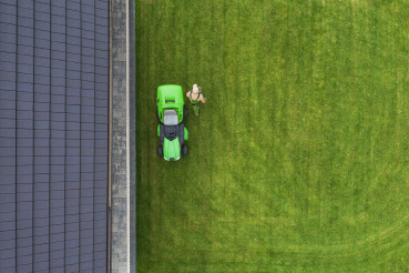 Aerial View of Riding Lawn Mower and Caucasian Gardener.