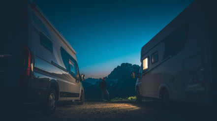 Alpine Camping Pitch and Men Between Two RVs Camper Vans