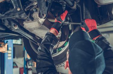 Automotive Caucasian Mechanic Working Under a Vehicle