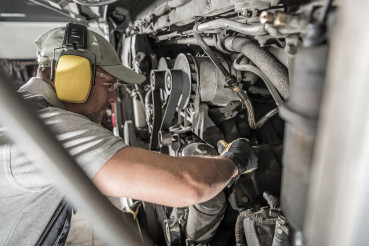 Automotive Mechanic Looking Inside Engine Compartment
