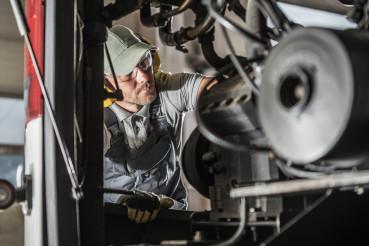 Automotive Mechanic Performing Scheduled Diesel Engine Service