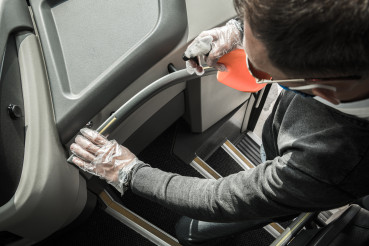 Bus Driver Sanitizing Railings Using Alcohol in Spray