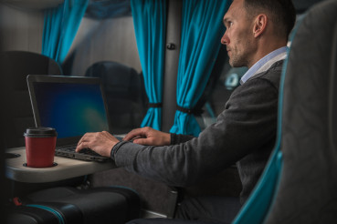 Businessman Working on His Laptop Computer During Coach Bus Road Trip