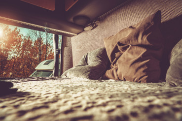 Camper Van Motorhome Comfortable Bed with the Outdoor View.