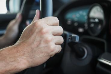 Hands On Steering Wheel Of Car.