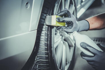 Car Detailing Worker Taking Care of Vehicle Tires and Alloy Wheels