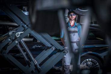 Car Mechanic Between Lifts