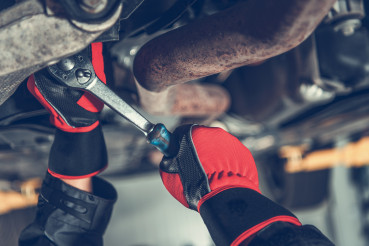 Car Mechanic Repairs Modern Vehicle Suspension Element