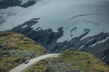 Car on the Dramatic Alpine Road with Glaciers