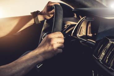Caucasian Driver Behind Exotic Car Steering Wheel