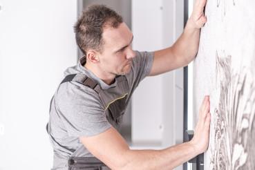 Caucasian Men Installing Wallpaper on His Bedroom's Wall