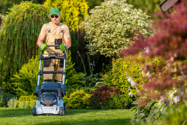 Caucasian Men Mowing Grass in His Garden